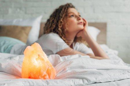 nachdenkliches Mädchen, das mit Himalaya-Salzlampe im Bett liegt, selektiver Fokus