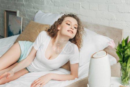 Photo pour Belle fille heureuse sur le lit avec purificateur d'air - image libre de droit