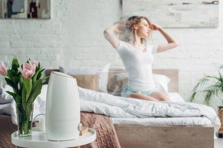Photo pour Foyer sélectif de la fille assise dans la chambre avec des fleurs de tulipe et purificateur d'air propagation de la vapeur - image libre de droit