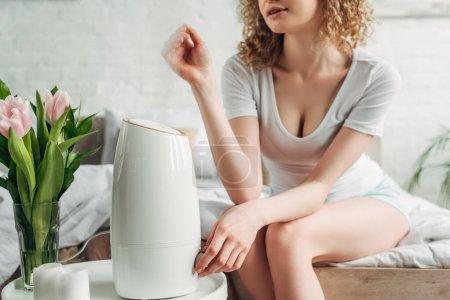 Photo pour Vue recadrée de fille assise dans la chambre avec purificateur d'air et fleurs de tulipe - image libre de droit