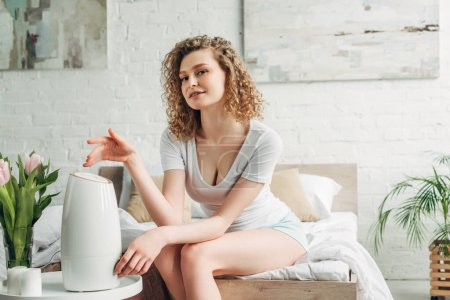 Photo pour Belle fille souriante assise dans la chambre avec purificateur d'air et tulipes - image libre de droit