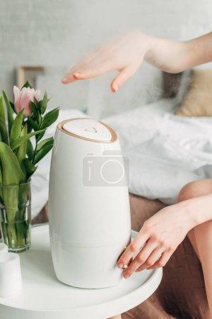 Photo pour Vue recadrée des mains féminines avec tulipes et purificateur d'air propageant la vapeur - image libre de droit