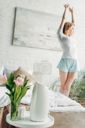 Photo pour Femme étirant dans la chambre avec purificateur d'air et fleurs, foyer sélectif - image libre de droit