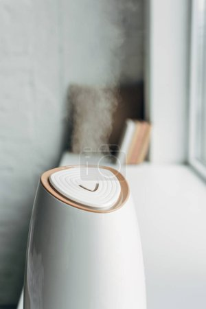 Photo pour Humidificateur répandant la vapeur et debout sur le rebord de la fenêtre à la maison - image libre de droit