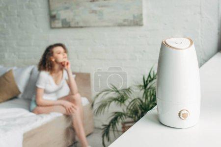 Photo pour Foyer sélectif de fille attrayante assise sur le lit avec purificateur d'air sur le rebord de la fenêtre - image libre de droit
