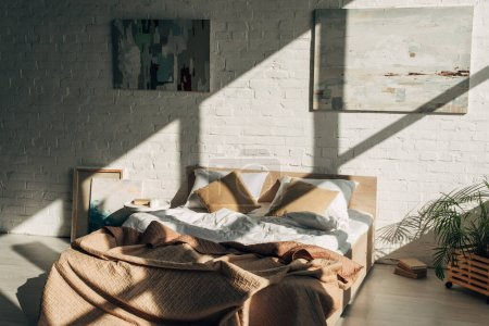 Photo for Bedroom interior with bed, pillows and paintings in sunlight with shadows - Royalty Free Image