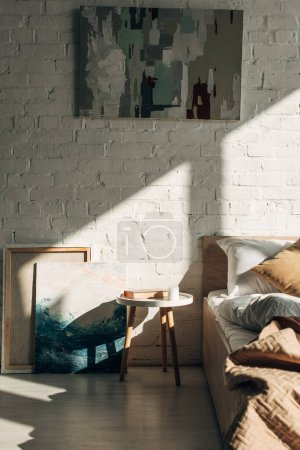 Photo for Bedroom interior with pillows and paintings in sunlight with shadows - Royalty Free Image