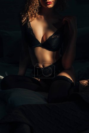 passionate young woman in black lingerie on bed in sunlight