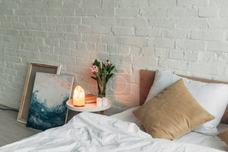 Schlafzimmereinrichtung mit Himalaya-Salzlampe, Blumen und Kerzen