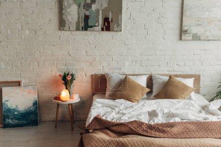 Photo pour Intérieur de la chambre avec lit, lampe de sel himalayenne, tulipes et peintures - image libre de droit