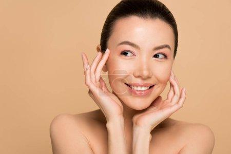 Photo pour Attractive souriante tendre femme asiatique nue avec peau parfaite isolée sur beige - image libre de droit
