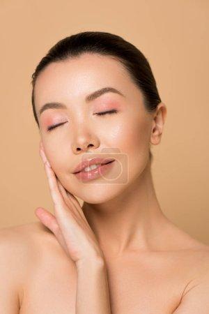 Photo pour Belle tendre asiatique fille avec propre visage et les yeux fermés isolé sur beige - image libre de droit