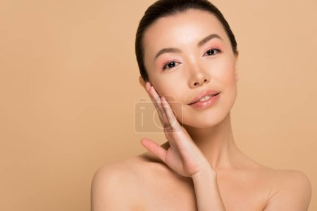 attractive tender naked asian girl with clean face isolated on beige
