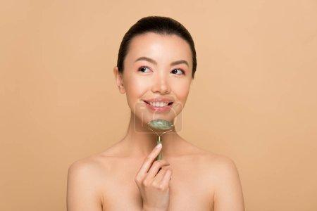 Photo pour Belle gai asiatique fille faire massage de visage avec jade rouleau isolé sur beige - image libre de droit