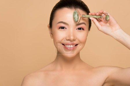 Photo pour Belle nu asiatique femme faire massage de visage avec jade rouleau isolé sur beige - image libre de droit
