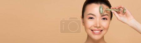 Photo pour Plan panoramique de belle fille asiatique souriante faisant massage du visage avec rouleau de jade isolé sur beige - image libre de droit
