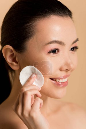 Photo pour Souriant asiatique fille démaquillage à partir de visage avec coton pad isolé sur beige - image libre de droit