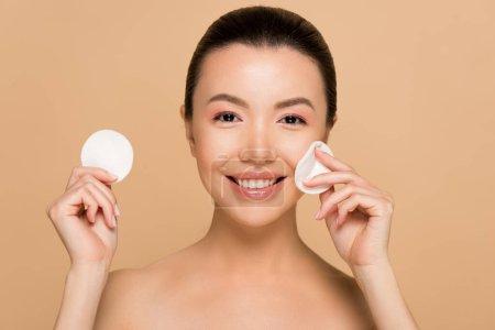 Photo pour Sourire nu asiatique fille démaquillage à partir du visage avec des tampons de coton isolé sur beige - image libre de droit