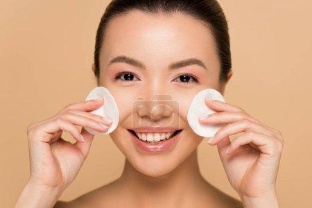 Photo pour Souriant asiatique femme démaquillage à partir du visage avec des tampons de coton isolé sur beige - image libre de droit