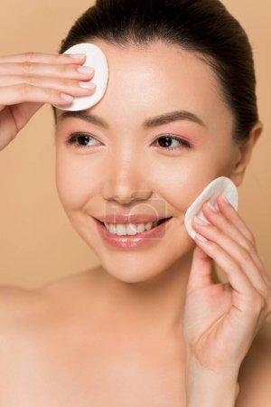 Photo pour Belle femme asiatique heureuse démaquillage du visage avec des coussinets de coton isolés sur beige - image libre de droit