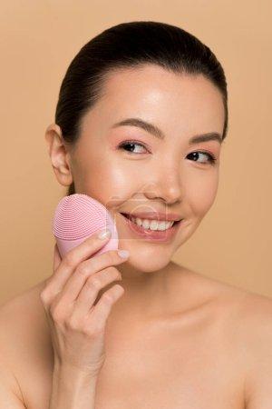 Foto de Niñas asiáticas desnudas atractivas que utilizan cepillo facial limpiador de silicona rosa aislado en beige. - Imagen libre de derechos