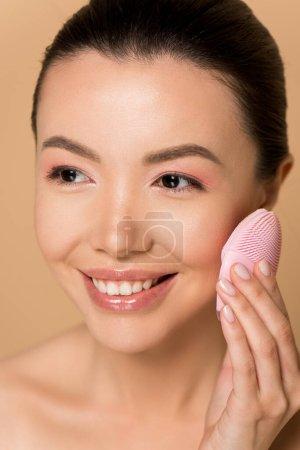 Foto de Hermosa chica asiática que sonríe desnuda usando cepillo facial limpiador de silicona aislado en beige. - Imagen libre de derechos