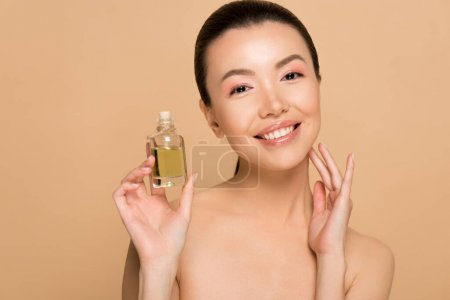 Photo for Attractive cheerful nude asian girl applying oil on face isolated on beige - Royalty Free Image