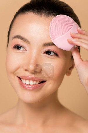 Foto de Seductora chica asiática sonriente que utiliza cepillo facial limpiador de silicona rosa aislado en beige. - Imagen libre de derechos