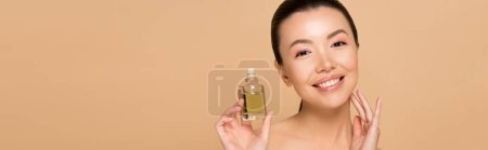 Photo for Panoramic shot of beautiful cheerful nude asian girl applying perfume on skin isolated on beige - Royalty Free Image