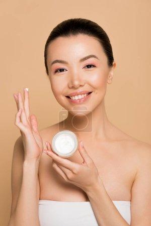 Photo pour Attrayant sourire asiatique fille tenant récipient en verre avec crème hydratante isolé sur beige - image libre de droit