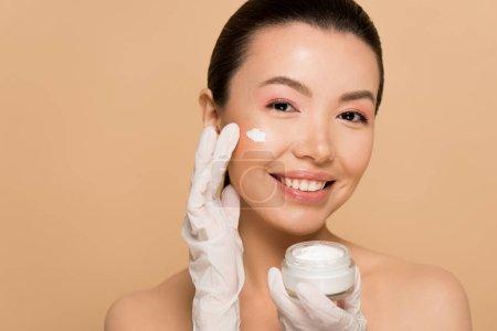 Photo pour Attrayant gai nu asiatique fille en latex gants application visage crème isolé sur beige - image libre de droit