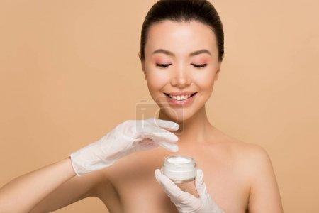 Photo pour Attrayante jeune fille asiatique nue dans des gants de latex appliquant de la crème pour le visage isolée sur beige - image libre de droit