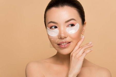Photo pour Belle tendre nu asiatique fille avec collagène eye pads isolé sur beige - image libre de droit