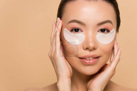 Photo pour Attrayant tendre asiatique femme avec collagène eye pads isolé sur beige - image libre de droit