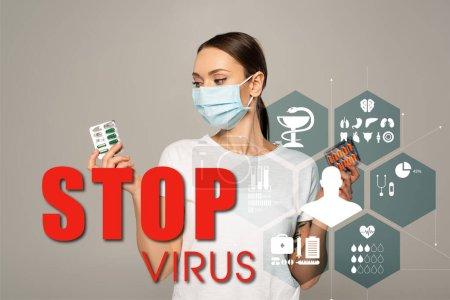 Photo pour Jeune femme tenant des ampoules avec des pilules isolées sur gris, arrêter le lettrage du virus et l'illustration des signes médicaux - image libre de droit
