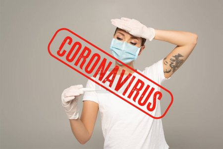 Photo pour Femme en masque médical en gants de latex tenant un thermomètre et touchant le front isolé sur gris, illustration du coronavirus - image libre de droit