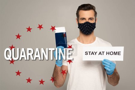 Photo for Man in safety mask and latex gloves holding card with stay at home lettering and passport with air ticket isolated on grey, quarantine illustration - Royalty Free Image