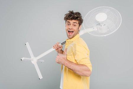 Photo pour Homme excité à bouche ouverte tenant un ventilateur électrique, regardant la caméra et montrant comme un signe isolé sur gris - image libre de droit