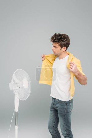 Photo pour Chemise homme touchante devant ventilateur électrique isolé sur gris - image libre de droit