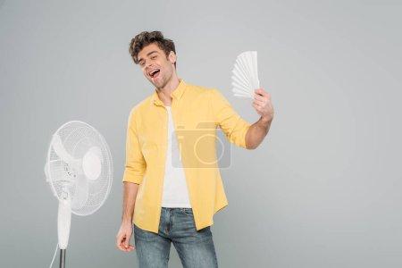 Photo pour Homme excité avec ventilateurs électriques et manuels souriant et regardant la caméra isolée sur gris - image libre de droit