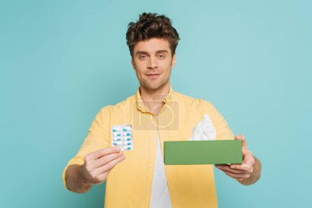 Photo for Front view of man showing blister pack with pills and box with napkins and looking at camera isolated on blue - Royalty Free Image