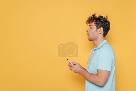 Photo pour Vue latérale de l'homme tenant la télécommande isolée sur jaune - image libre de droit
