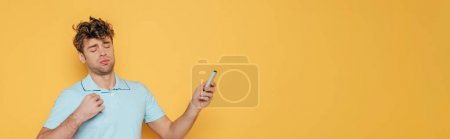 Photo for Man with remote controller in outstretched hand suffering from heat isolated on yellow, panoramic shot - Royalty Free Image