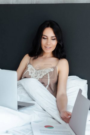 positive woman working with business documents and laptop in bed on self isolation
