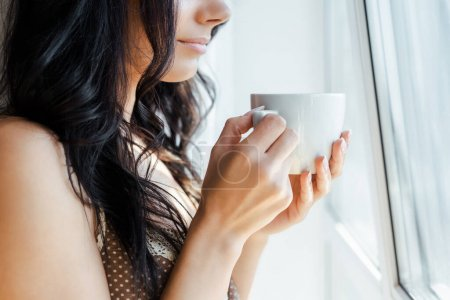 Photo for Cropped view of girl holding cup of coffee near window - Royalty Free Image