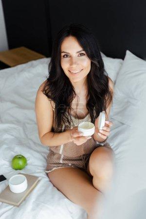 Photo pour Belle fille souriante tenant crème visage tout en étant assis sur le lit avec des conteneurs en plastique et pomme - image libre de droit
