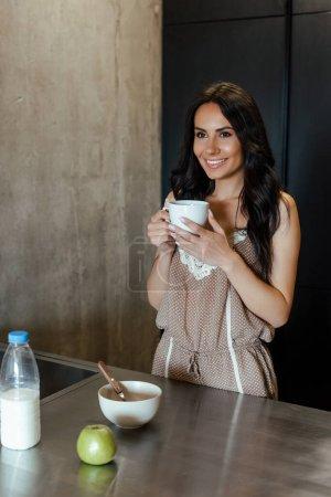 Photo pour Belle femme souriante avec une tasse de café au petit déjeuner dans la cuisine le matin - image libre de droit