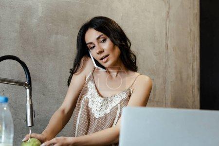 Photo pour Belle femme parlant sur smartphone, regardant l'ordinateur portable et laver la pomme pendant le petit déjeuner dans la cuisine - image libre de droit