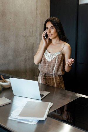 jeune femme parlant sur smartphone et utilisant un ordinateur portable pendant le petit déjeuner sur la cuisine avec des documents d'affaires