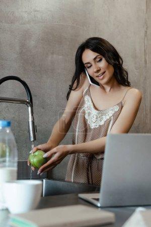 Photo pour Une femme souriante parlant sur un téléphone intelligent et utilisant un ordinateur portable pendant qu'elle lave une pomme dans la cuisine - image libre de droit